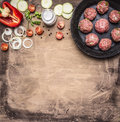 Meat balls with herbs and onions in a pan with tomatoes, peppers, zucchini and herbs on wooden rustic background top view close up Royalty Free Stock Photo