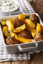 Meat balls with potato wedges in a baking dish and sour cream cl Royalty Free Stock Photo