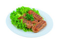 Meat cutlets fried on the grill, lay on the leaves of lettuce on a white plate. Royalty Free Stock Photo