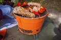 Meat grilling over the coals on a portable barbecue