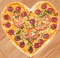 Meat pizza with ham in heart shape for valentine salami tomatoes and cheese topped fresh italian herbs Royalty Free Stock Photography