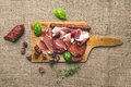 Meat plate on rustic wood board over a rough sackcloth backgroun Royalty Free Stock Photo