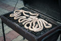 Meat sausages cooking on a charcoal grill in garden Royalty Free Stock Photo