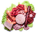 Meat and sausages on lettuce leaves. Royalty Free Stock Photo