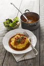 Meat sause served on polenta on a white plate with salad Stock Image