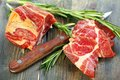 Meat and sprigs rosemary closeup tasty sprig of on a wooden table Royalty Free Stock Photo