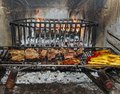 Meat and vegetables are cooked on the grill in a large fireplace in the restaurant Stock Images