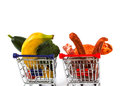 Meat and vegetables in two shopping carts isolated on white one is full with one with stand side by side Stock Photography