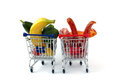 Meat and vegetables in two shopping carts isolated on white one is full with one with stand side by side Stock Photos