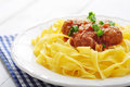 Meatballs with pasta and parmesan in white plate on wooden background Stock Photography