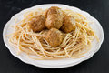 Meatballs with spaghetti in white plate on black background Stock Photos