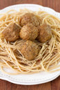 Meatballs with spaghetti in white plate on brown background Stock Image