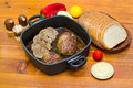 Meatloaf bread and vegetables in pan in basket on old wooden table Royalty Free Stock Photo