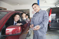 Mecánico helping family con su coche Imagen de archivo libre de regalías