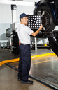 Mechanic adjusting wheel alignment machine full length of male on car in garage Royalty Free Stock Photo