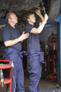 Mechanic and apprentice working on car Royalty Free Stock Image