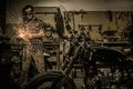 Mechanic building customs motorcycle doing lathe works in garage Royalty Free Stock Image
