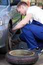Mechanic changing flat tyre young during vertical Stock Images