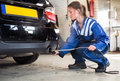 Mechanic checking diesel exhaust emission rates female probing a sensor into the of a car measuring the carbondioxide levels and Stock Image
