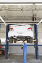 Mechanic checking underneath car on a lift Royalty Free Stock Image