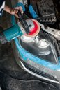 Mechanic cleaning headlights with polishing power buffer machine and tools Stock Image