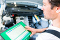 Mechanic with diagnostic tool in car workshop Royalty Free Stock Image