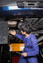Mechanic examining underneath car lifted at auto repair shop Stock Photography