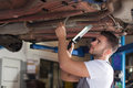 Mechanic fixing car chassis focused man holding a lamp and a under the Royalty Free Stock Images
