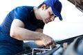 Mechanic fixing a car engine Royalty Free Stock Photo