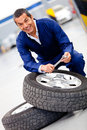 Mechanic fixing car tire Royalty Free Stock Image