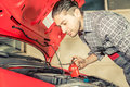 Mechanic fixing and checking a car working in the hood Royalty Free Stock Photo