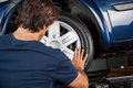 Mechanic fixing hubcap to car tire rear view of male at garage Stock Photo
