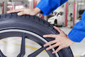 Mechanic hands pushing tire at workshop Royalty Free Stock Photo