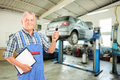 Mechanic holding a car key atauto repair shop during an automobi Royalty Free Stock Photos