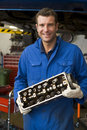 Mechanic holding car part smiling Royalty Free Stock Images
