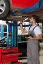 Mechanic making an inspection of a car chassis focused standing under holding digital tablet in one hand in other hand holding Stock Image
