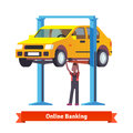 Mechanic repairing a car lifted on auto hoist Royalty Free Stock Photo