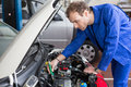 Mechanic repairing motor electric parts car garage Royalty Free Stock Photography