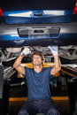 Mechanic repairing underneath car male lifted at garage Stock Images