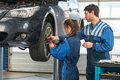 Mechanic teaching an intern in a garage the best practice learning on the job during practical internship Royalty Free Stock Photo