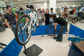 Mechanic teaching people how to inflate a tire at bicycle repair workshop in decathlon store Stock Photo