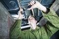 Mechanic under car tightening with ratchet platform Stock Photo
