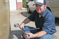 Mechanic using a tire iron to remove lug nuts from an automobile tire Stock Photography