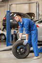 Mechanic with wheel tire at car workshop Royalty Free Stock Photo