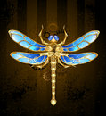 Mechanical dragonfly brass and gold with wings decorated with blue glass and gears Royalty Free Stock Photos