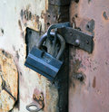 Mechanical hinged lock the on old crumpled of a door of garage Royalty Free Stock Photo