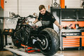 Mechanician changing motorcycle wheel in bike repair shop. Royalty Free Stock Photo