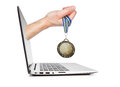 Medal winner in the man s hand sticking out of the laptop concept idea Royalty Free Stock Image