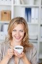 Mediados de empresaria adulta holding coffee cup en oficina Imagen de archivo libre de regalías