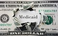 Medicaid costs hole torn in a dollar bill with text Stock Photos